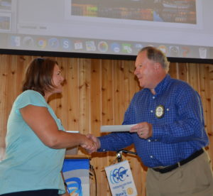 Spike present a NRF check to Michelle Bechtold for the Rotary Student Exchange Program partnership 081716